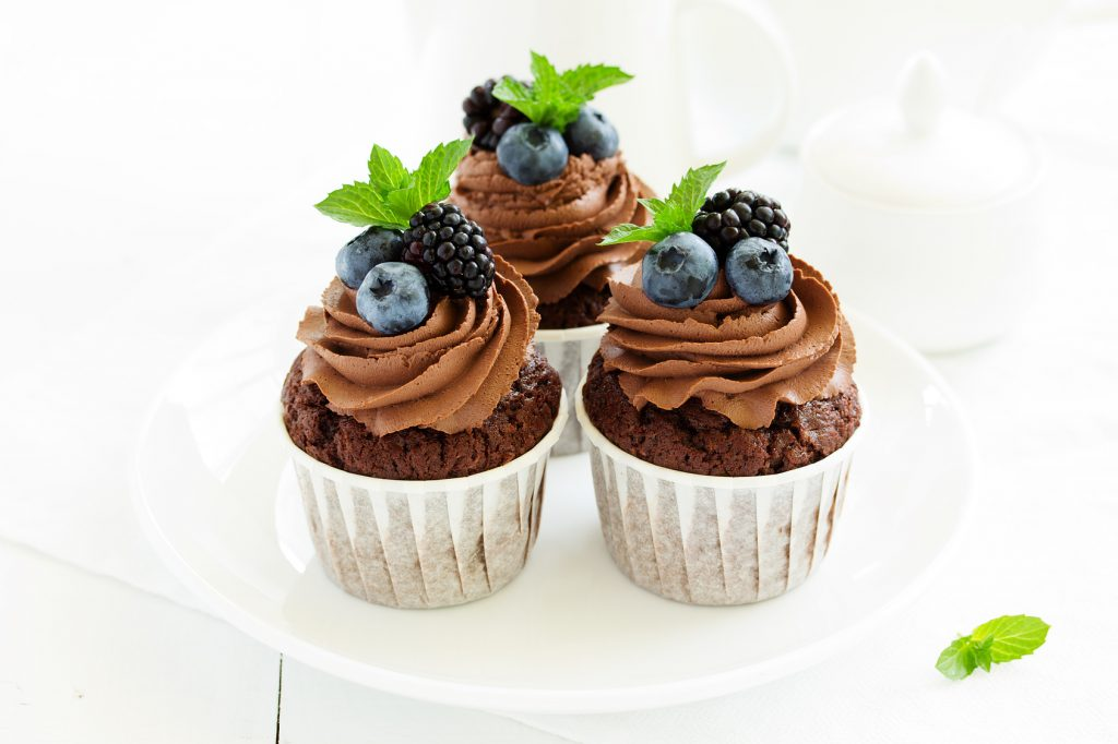 Chocolate cupcakes, with chocolate cream and fresh berries.